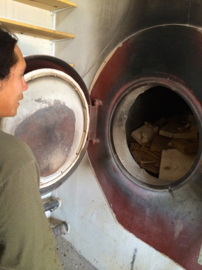 Angelo McHorse showing us the GARN biomass furnace. Photo by Elizabeth Hoover