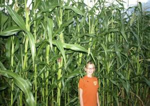 Caidlen Dunham of Jay, Okla., stands in front of Cherokee flour corn planted from seeds distributed by the Cherokee Nation. Photo courtesy of the Cherokee Phoenix.
