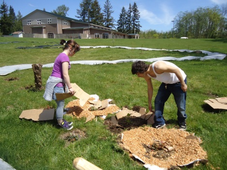 In 2010 Angelo brought Native students from the Big Picture school in Seattle to help with the construction of the berry garden. Here Cassie and Jake are laying out sheet mulching that will keep down weeds once the berry bushes are planted. Photo by Angelo Baca