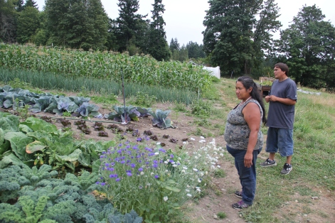 Grace Ann Byrd and Julian surveying kale and cabbages at the Nisqually Community Garden