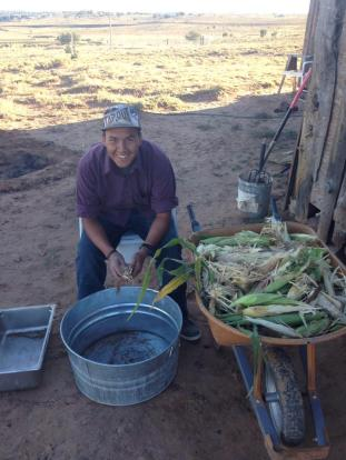 Ty Tsosie husking corn. September 28. Photo by Roberto Nutlouis