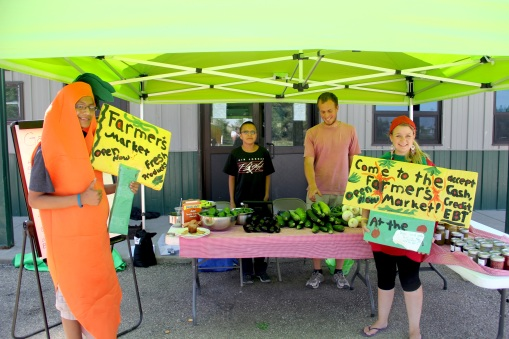 Aryan Iron Moccasin (as a carrot), garden intern Luta, sustainable agriculture manager Ryan Devlin, and Trina, a volunteer from Germany who spent the summer working with CRYP. Photo by Angelo Baca
