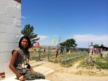 Justin Rowland, a descendant of survivors of the Wounded Knee massacre, sits at the Wounded Knee Memorial. Behind him is a mass grave of those killed. Photo by Elizabeth Hoover
