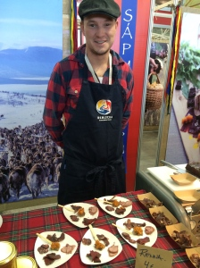 Sami reindeer herder from Sweden, with sample of cured reindeer meat and cloudberry jam. Photo by Elizabeth Hoover