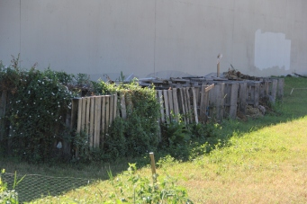Compost bins along the sound wall. Photo by Angelo Baca