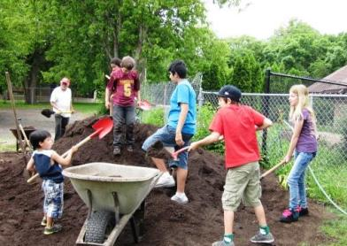Kids helping to shovel 47 tons of compost, spring 2013. Photo courtesy of the Women's Environmental Institute