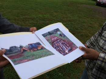 Danny Powless shows us photos of the construction of the hugelkultur bed last year. Photo of the photos by Elizabeth Hoover