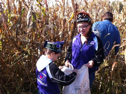 Oneida Nation powwow princesses picking white corn. Photo by Elizabeth Hoover (October 2013)