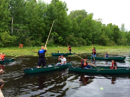 Learning how to use a pole to move the canoe slowly along. Photo by Elizabeth Hoover