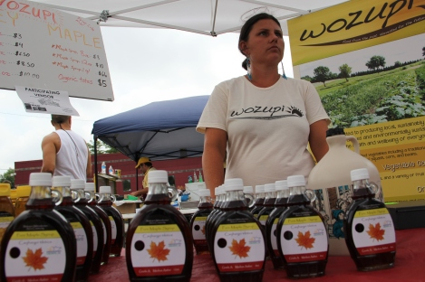 Wozupi director Rebecca Yoshino selling syrup at the farmers market. Photo by Angelo Baca