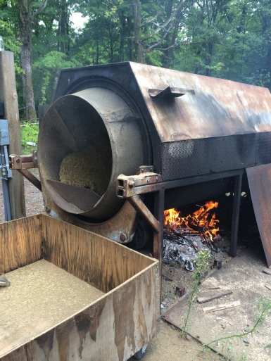 The fresh rice is then fed into this apparatus. The inside tube has specially designed fins that makes sure the rice moves evenly as the tube rotates over the fire. Photo by Elizabeth Hoover 8/30/14