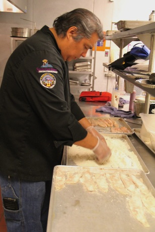 Arlie breading walleye donated by the Red Lake tribe, in finely ground Oneida white corn flour. Photo by Elizabeth Hoover