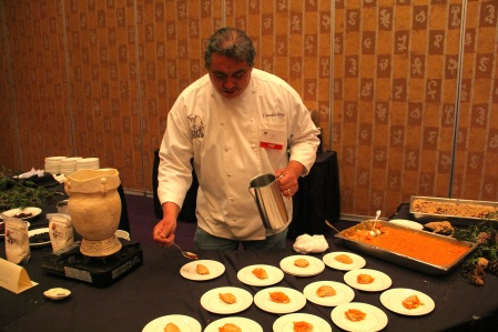 "Arlie drizzling maple syrup over ""Onyu'sha otsiskwa' okhale wa'hta o'hses"", white corn pudding with squash. Photo by Elizabeth Hoover"