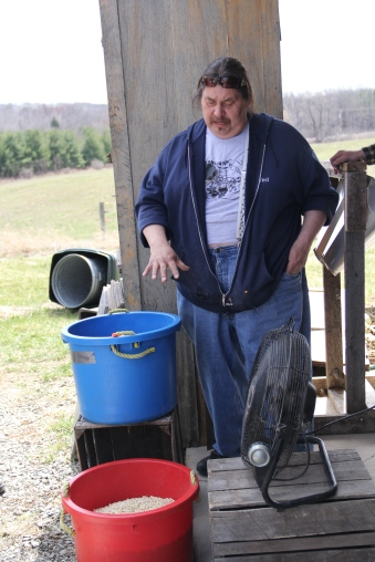 Ted Skennandore (Oneida), demonstrating winnowing corn, to blow away chaff from the kernels that will become food or be saved for seed. Photo by Elizabeth Hoover