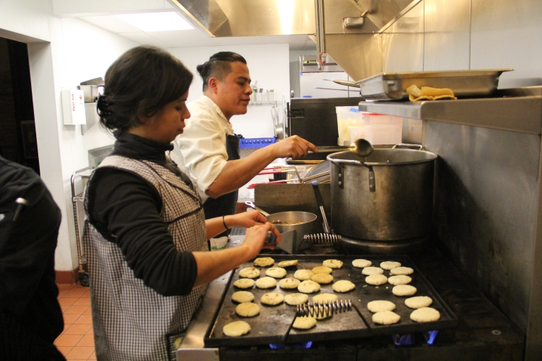 Marlene making gorditas from yucca flour while Neftali stirs the posole. Photo by Elizabeth Hoover